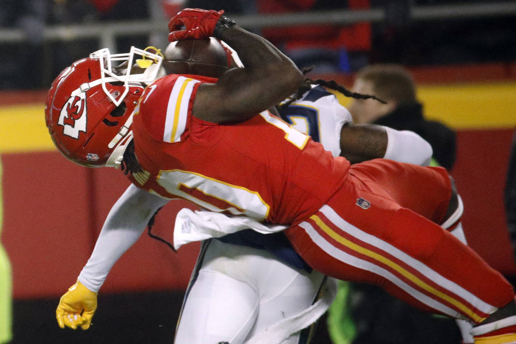 Kansas City Chiefs wide receiver Tyreek Hill (10) is hit by Los Angeles Chargers safety Jahleel Addae (37) while making a catch during the second half of an NFL football game in Kansas City, Mo., ...