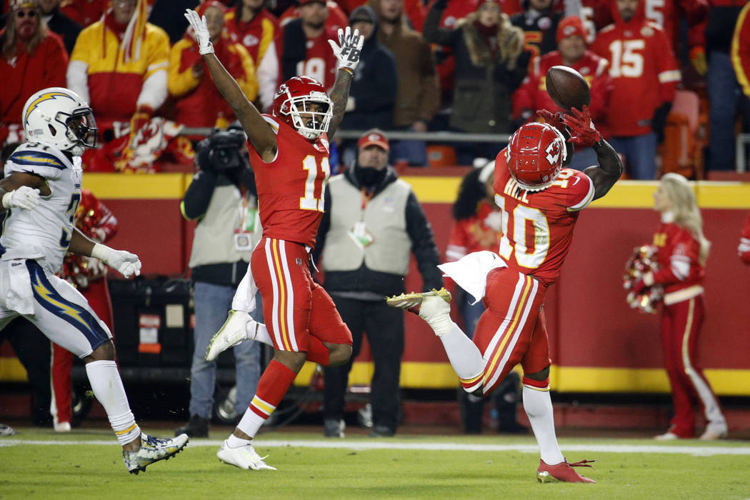 Kansas City Chiefs wide receiver Demarcus Robinson (11) gestures as the ball bounces off the helmet of wide receiver Tyreek Hill (10) during the second half of an NFL football game against the Los ...