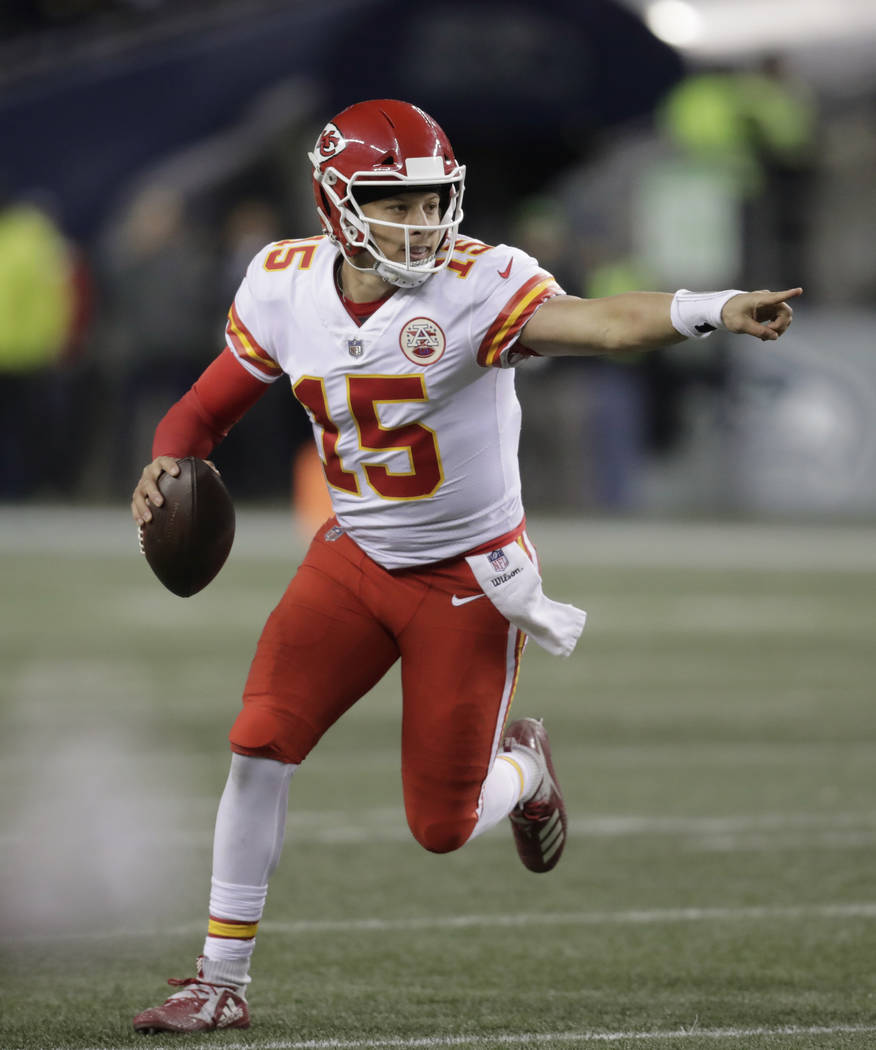 Kansas City Chiefs quarterback Patrick Mahomes scrambles with the ball during the second half of an NFL football game against the Seattle Seahawks, Sunday, Dec. 23, 2018, in Seattle. (AP Photo/Ste ...