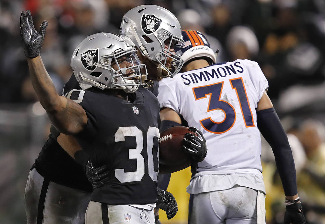 Oakland Raiders running back Jalen Richard (30) celebrates with Lee Smith after scoring a touchdown in front of Denver Broncos free safety Justin Simmons (31) during the second half of an NFL foot ...