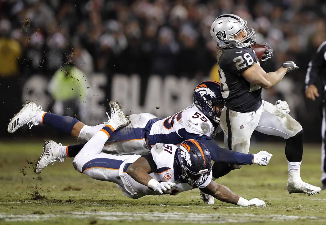 Oakland Raiders running back Doug Martin (28) runs against Denver Broncos outside linebacker Bradley Chubb (55) and inside linebacker Todd Davis (51) during the second half of an NFL football game ...