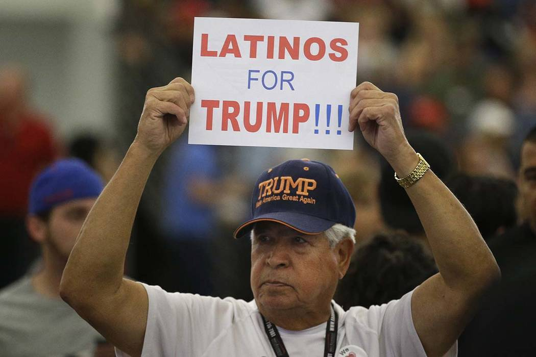 A man holds up a sign for then-Republican presidential candidate Donald Trump before the start of a May 25, 2016, rally at the Anaheim Convention Center. Republicans are holding onto a steady shar ...
