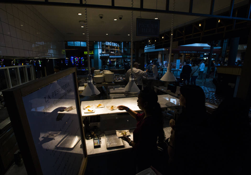 People try food from La Pescheria before the ribbon cutting ceremony for Eataly at Park MGM in Las Vegas on Thursday, Dec. 27, 2018. Chase Stevens Las Vegas Review-Journal @csstevensphoto