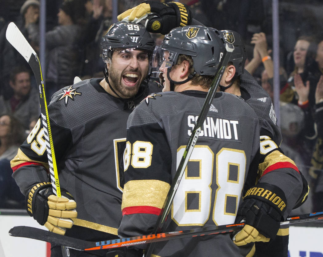 Golden Knights right wing Alex Tuch (89) celebrates with teammate Nate Schmidt (88) after assisting on a first period goal during Vegas' home matchup with the Colorado Avalanche on Thursday, Dec. ...