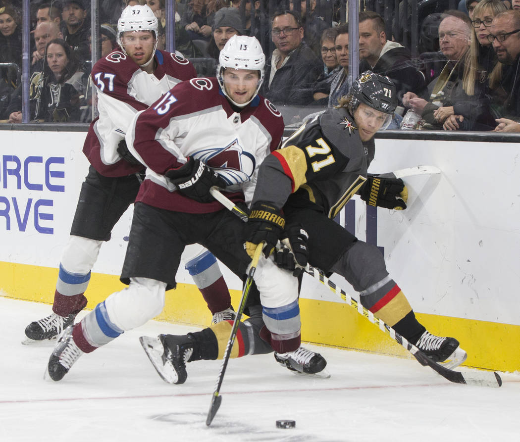 Golden Knights center William Karlsson (71) fights for a loose puck with Colorado Avalanche center Alexander Kerfoot (13) and left wing J.T. Compher (37) in the second period on Thursday, Dec. 27, ...