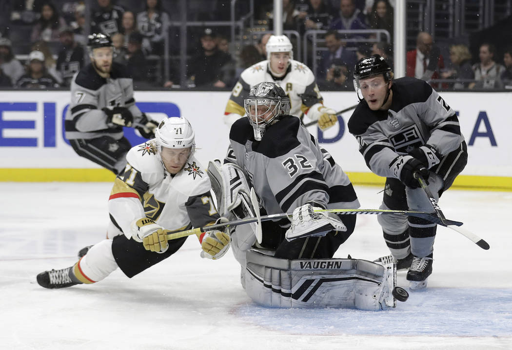 Los Angeles Kings goaltender Jonathan Quick, center, deflects a shot in front of Vegas Golden Knights' William Karlsson, left, during the first period of an NHL hockey game Saturday, Dec. 29, 2018 ...
