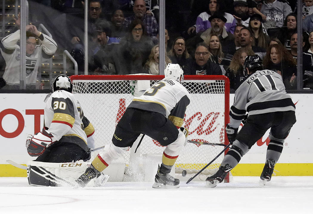 Los Angeles Kings center Anze Kopitar, right, scores past Vegas Golden Knights' Brayden McNabb, center, and goaltender Malcolm Subban (30) during the first period of an NHL hockey game Saturday, D ...