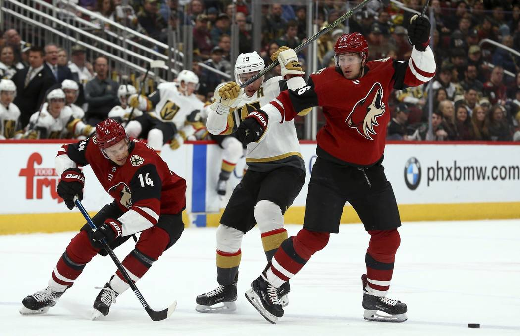 Arizona Coyotes right wing Richard Panik (14) skates around Vegas Golden Knights right wing Reilly Smith (19) and Coyotes defenseman Ilya Lyubushkin, right, to get to the puck during the first per ...