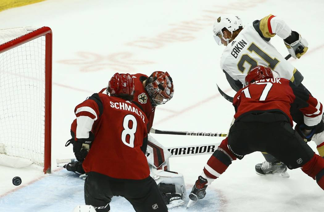 Vegas Golden Knights center Cody Eakin (21) sends the puck past Arizona Coyotes center Nick Schmaltz (8), center Alex Galchenyuk (17) and goaltender Darcy Kuemper, back left, for a goal during the ...