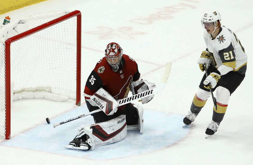 Arizona Coyotes goaltender Darcy Kuemper (35) gives up a goal to Vegas Golden Knights Ryan Carpenter as Golden Knights center Cody Eakin (21) looks on during the third period of an NHL hockey game ...