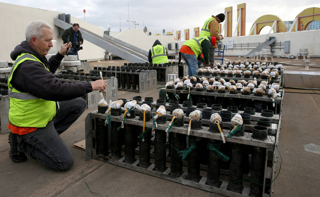 Technicians with Fireworks by Grucci, including Greg Bottomley, left, load pyrotechnics on the roof of Planet Hollywood in Las Vegas Friday, Dec. 27, 2018. More than 80,000 pyrotechnic effects wil ...
