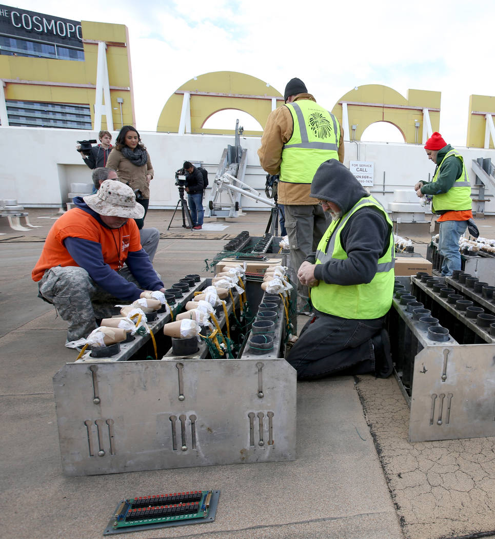 Technicians with Fireworks by Grucci, including Matthew Alberts, left, and Jim Giordano load pyrotechnics on the roof of Planet Hollywood in Las Vegas Friday, Dec. 27, 2018. More than 80,000 pyrot ...