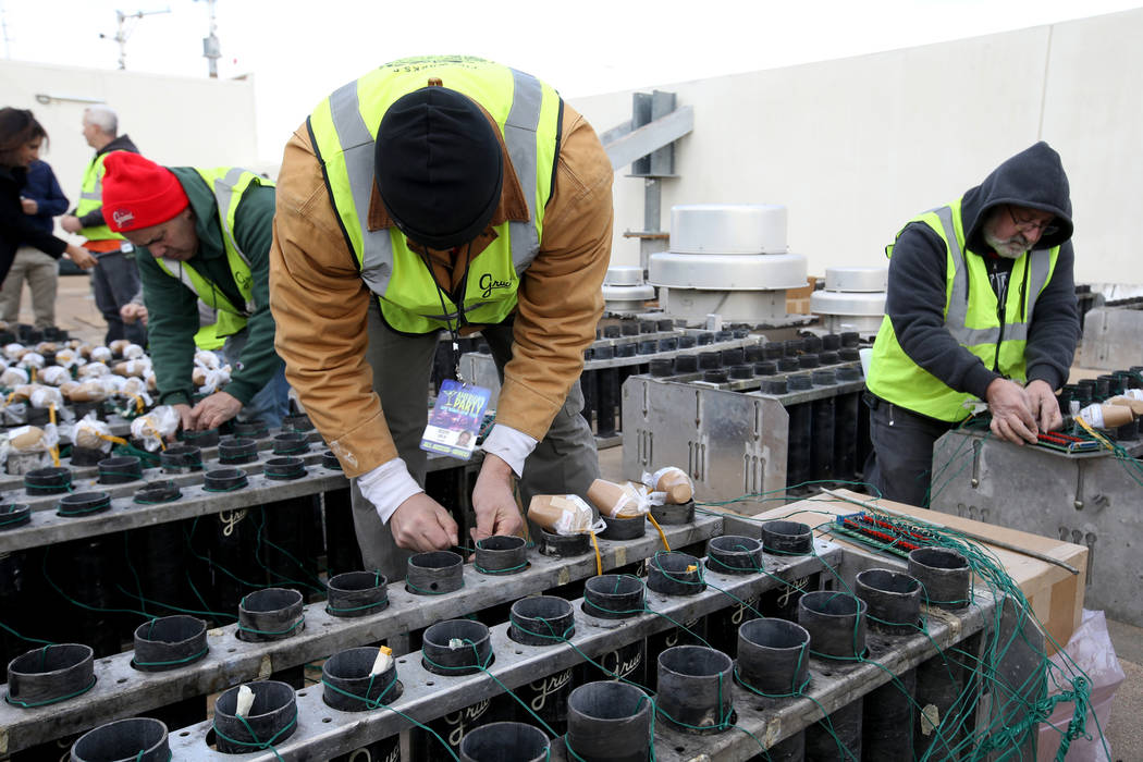 Technicians with Fireworks by Grucci, including, from left, Lou Deleo, Joseph Giglio, and Jim Giordano load pyrotechnics on the roof of Planet Hollywood in Las Vegas Friday, Dec. 27, 2018. More th ...