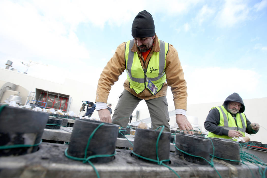 Technicians with Fireworks by Grucci, including Joseph Giglio, left, and Jim Giordano load pyrotechnics on the roof of Planet Hollywood in Las Vegas Friday, Dec. 27, 2018. More than 80,000 pyrotec ...