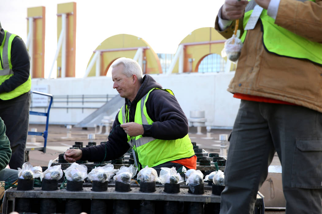 Technicians with Fireworks by Grucci, including Greg Bottomley, center, load pyrotechnics on the roof of Planet Hollywood in Las Vegas Friday, Dec. 27, 2018. More than 80,000 pyrotechnic effects w ...