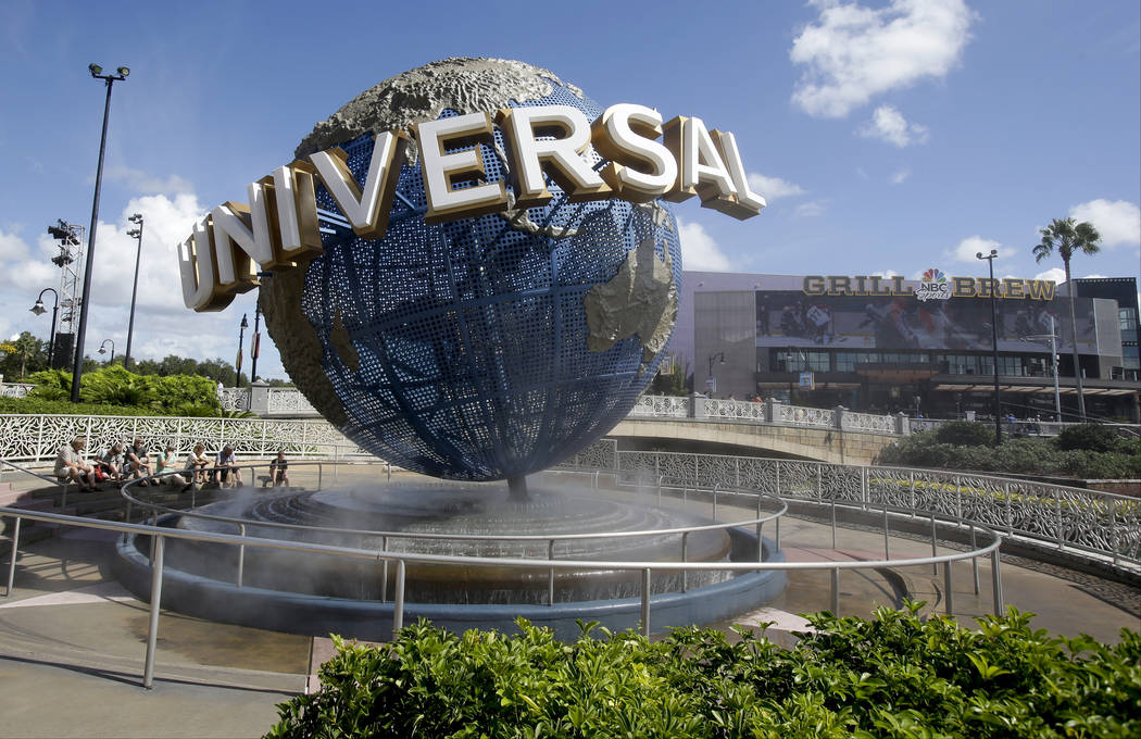 In this Oct. 22, 2015 file photo, park guests relax and cool off with a water mist under the globe at Universal Studios City Walk in Orlando, Fla. A lawsuit brought by a Guatemalan family whose fa ...