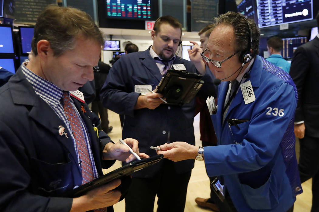 Traders Robert Charmak, Michael Milano, and Steven Kaplan, left to right, work on the floor of the New York Stock Exchange, Friday, Dec. 28, 2018. Stocks are opening higher Friday as U.S. markets ...