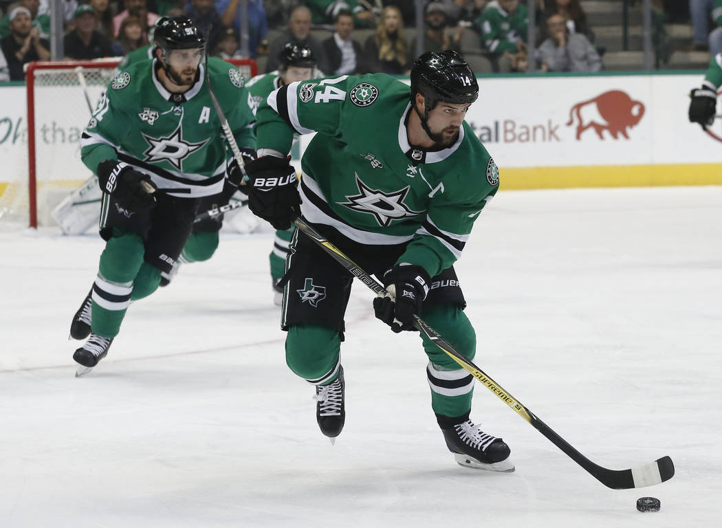 In this Oct. 21, 2017, file photo, Dallas Stars wing Jamie Benn skates the puck upice as center Tyler Seguin trails during the first period of an NHL hockey game against the Carolina Hurricanes in ...