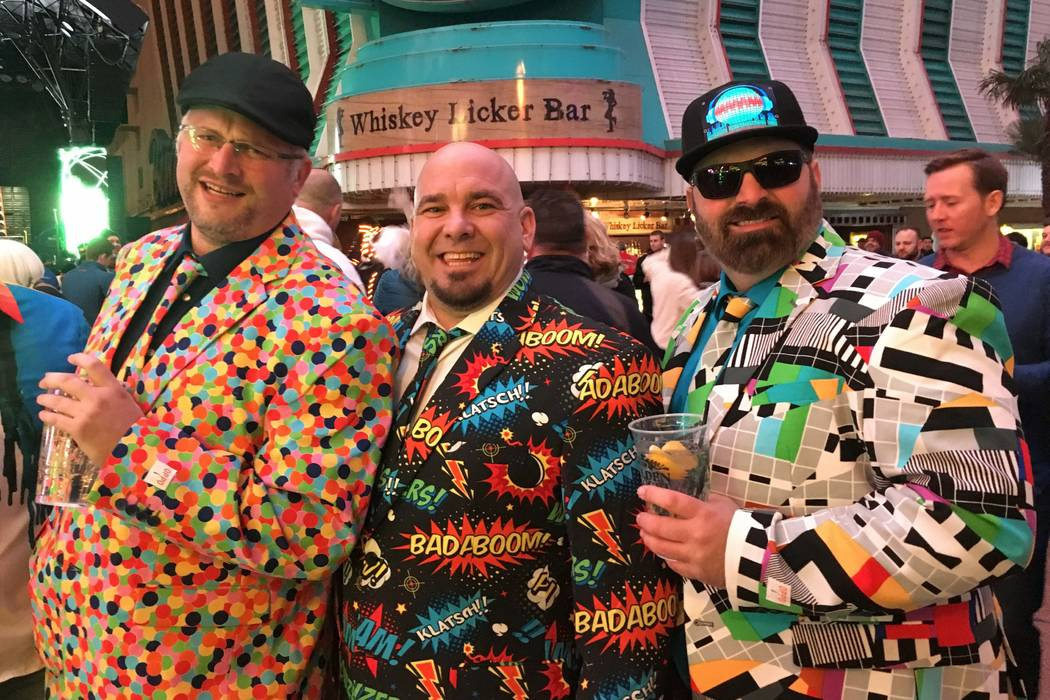 Brandon Vanvactor (left), Bob Crosby and Byron Guerra from South Bend, Indiana became their own attraction by sporting colorful suits purchased online while celebrating New Year's Eve on downtown ...