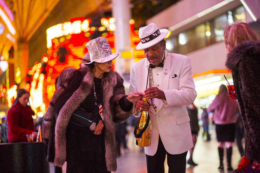 Frank and Cathy Clarke of California walk along the Fremont Street Experience as New Year's Eve revelers gather in downtown Las Vegas on Monday, Dec. 31, 2018. Chase Stevens Las Vegas Review-Journ ...