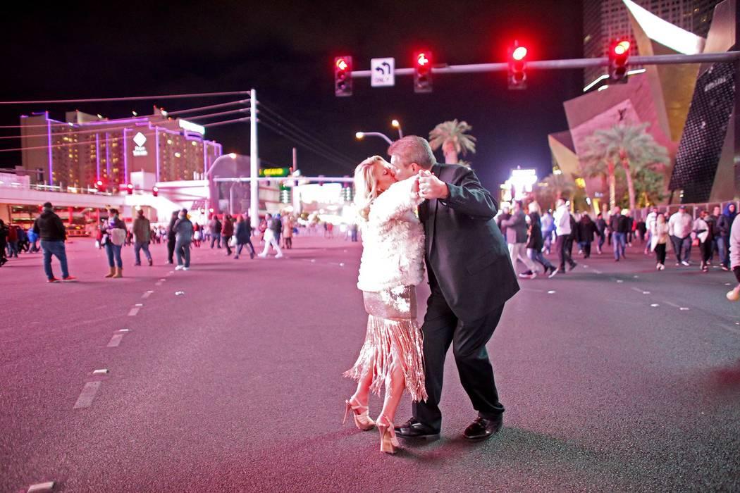 Dena Grabowki kisses her husband Jim Grabowski, both of Michigan, at the intersection of Harmon and Las Vegas Blvd. on Dec 31, 2018. (Rachel Aston/Las Vegas Review-Journal)