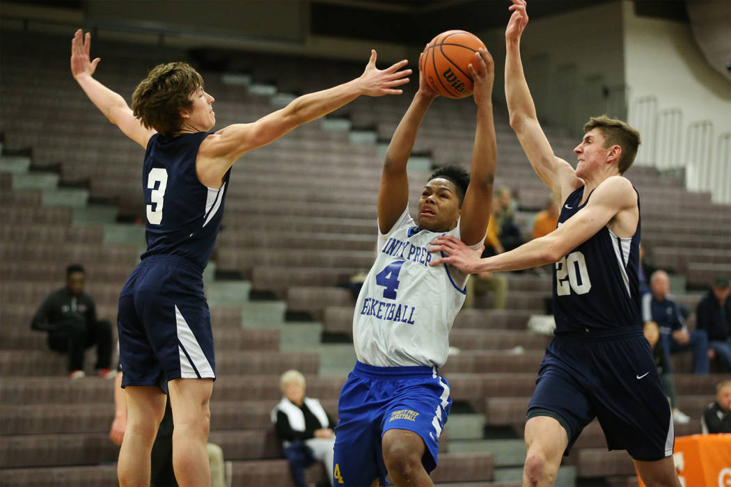 Trinity's Jose Cuello (4) drives the ball under pressure from Foothill's Collin Russell (3) and Caleb Stearman (20) in the Las Vegas Prep Championship seminal game at Las Vegas High School in Las ...