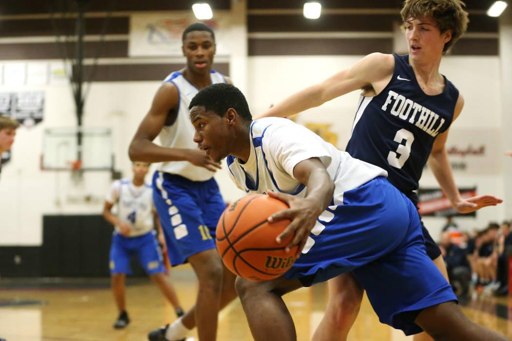 Trinity's Milton Burnett (15) drives the ball around Foothill's Collin Russell (3) in the Las Vegas Prep Championship seminal game at Las Vegas High School in Las Vegas, Friday, Dec. 28, 2018. Tri ...