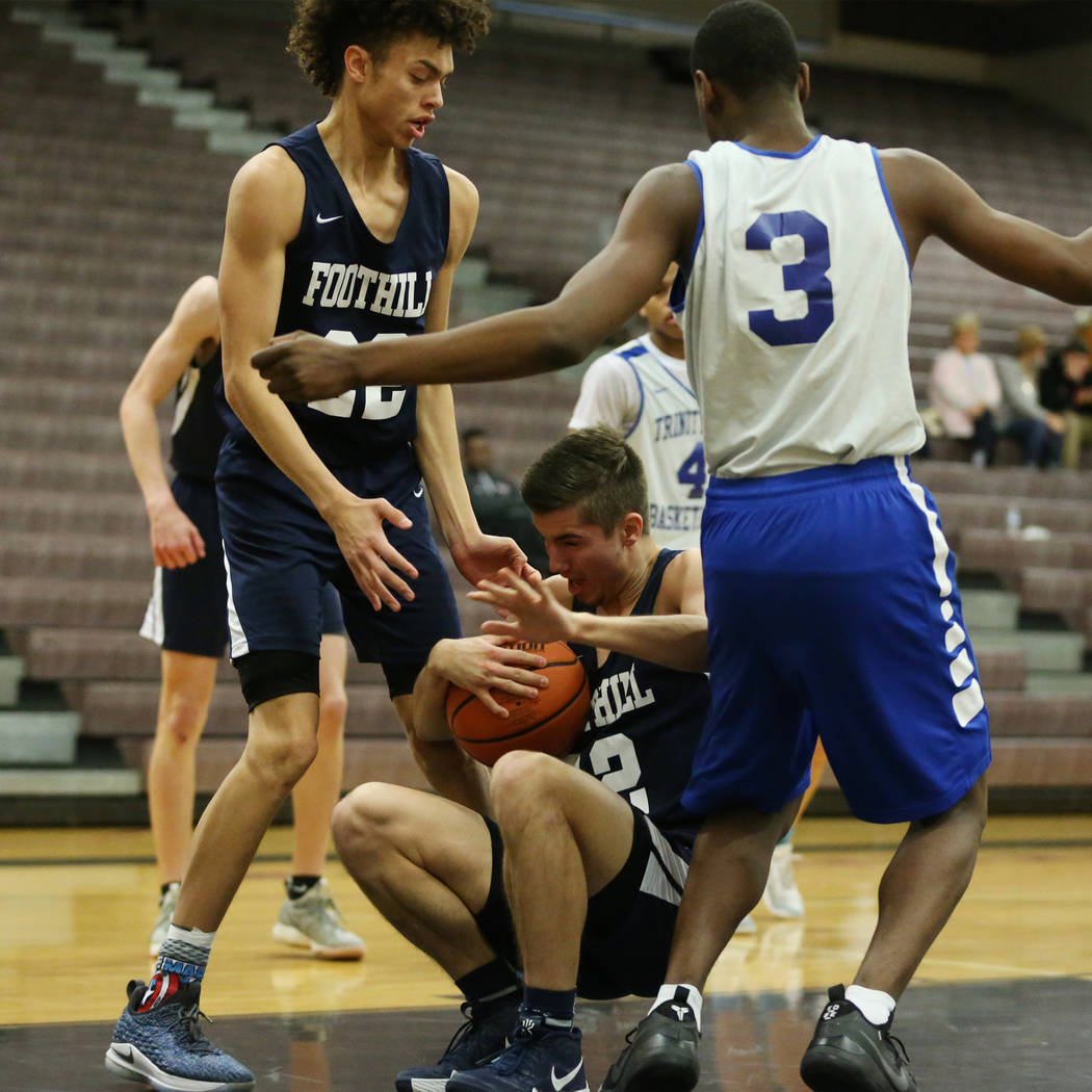 Foothill's Dylan Hushaw (32), with teammate Jace Rocequemore (22), takes a fall under pressure from Trinity's Kevin Giles (3) in the Las Vegas Prep Championship seminal game at Las Vegas High Scho ...