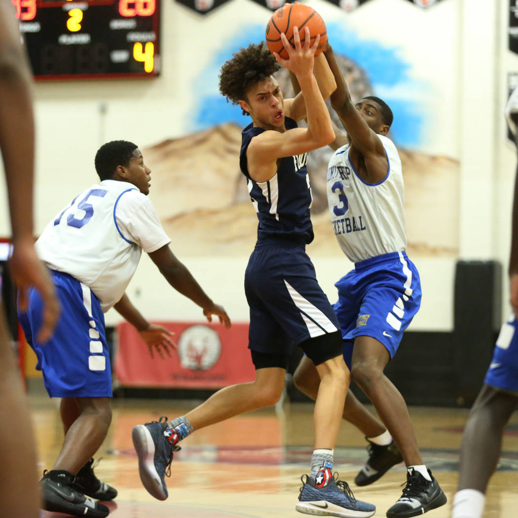 Foothill's Jace Rocequemore (22), center, is pressured by Trinity's Kevin Giles (3) in the Las Vegas Prep Championship seminal game at Las Vegas High School in Las Vegas, Friday, Dec. 28, 2018. Tr ...