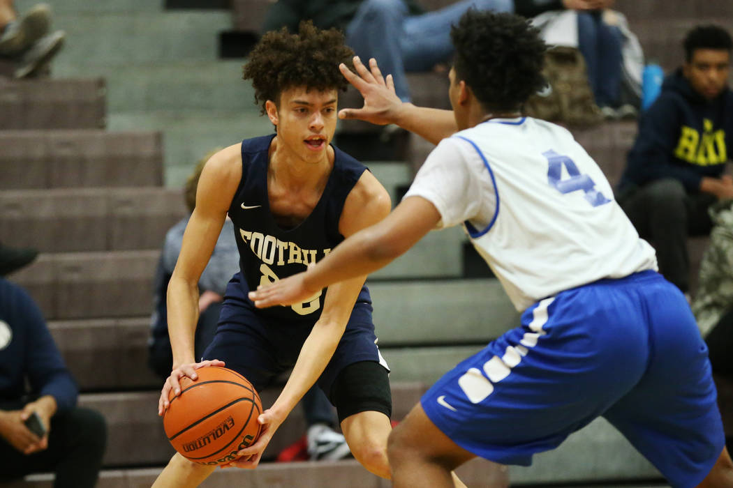 Foothill's Jace Rocequemore (22) looks for an open play against Trinity's Jose Cuello (4) in the Las Vegas Prep Championship seminal game at Las Vegas High School in Las Vegas, Friday, Dec. 28, 20 ...