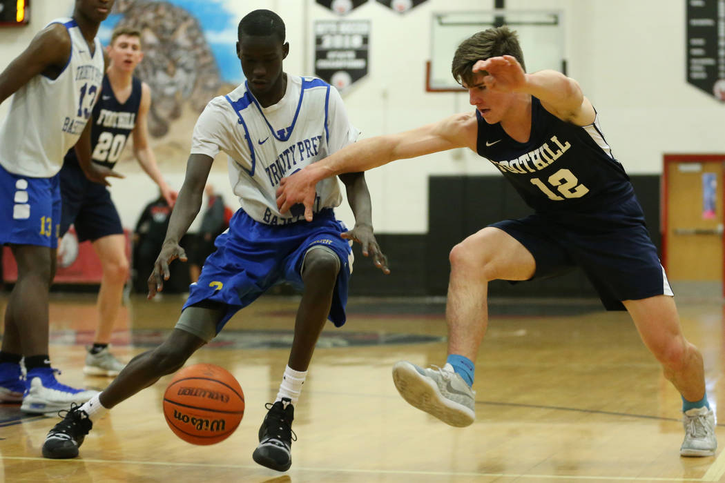 Trinity's Madait Mou (2) steals the ball from Foothill's Fisher Welch (12) in the Las Vegas Prep Championship seminal game at Las Vegas High School in Las Vegas, Friday, Dec. 28, 2018. Trinity won ...