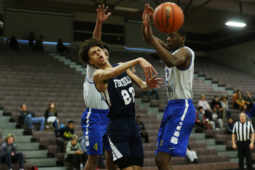 Foothill's Jace Rocequemore (22) makes a pass under pressure from Trinity's Kevin Giles (3) in the Las Vegas Prep Championship seminal game at Las Vegas High School in Las Vegas, Friday, Dec. 28, ...