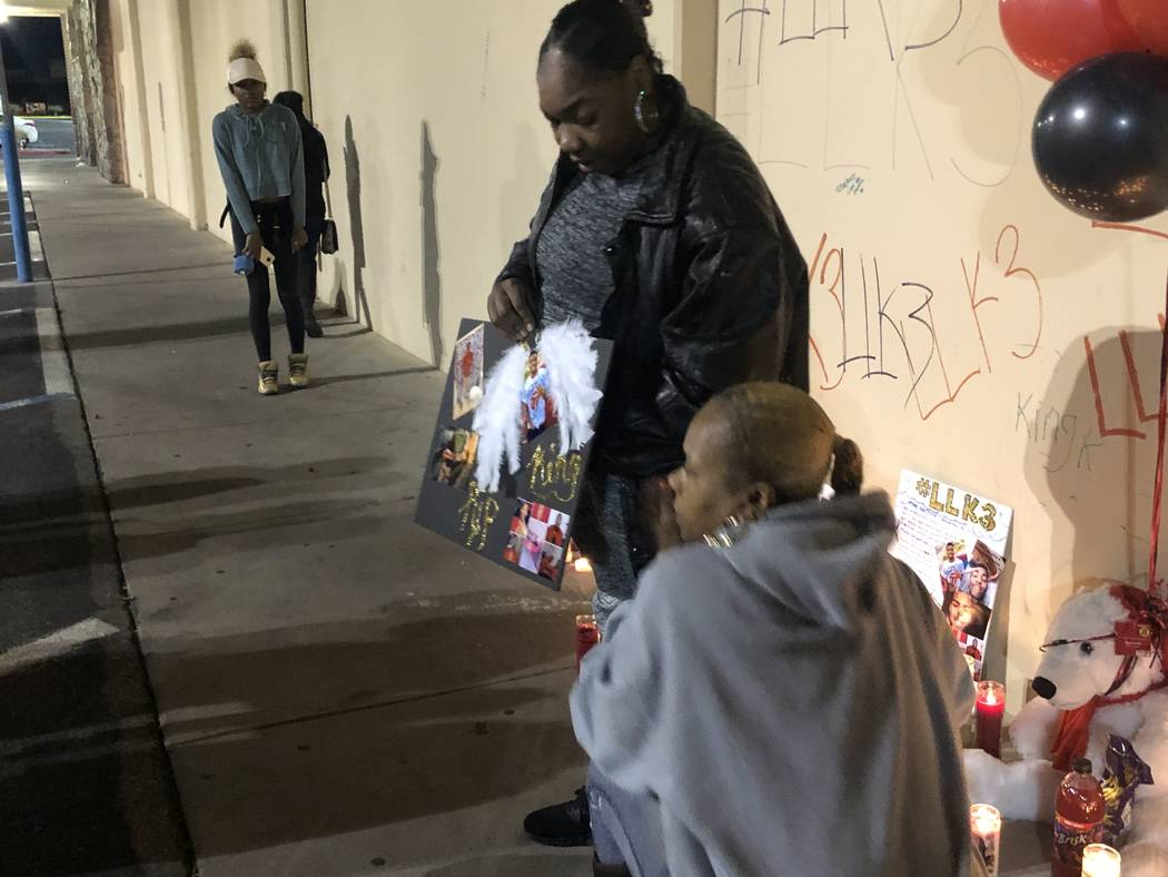 Timika Thomas stands and holds a posterboard decorated with angel wings and pictures of her son, 18-year-old Kwavon'tia Thomas, during a vigil on December 28, 2018. Thomas was shot in a parking lo ...