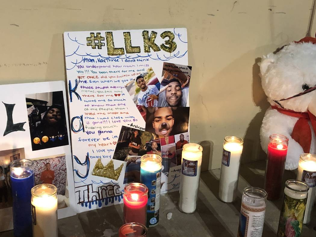 A poster board decorated with photos of 18-year-old Kwavon'tia Thomas is surrounded by candles during a vigil on Friday, December 28, 2018, where he was shot Christmas Eve in a parking lot near Ea ...