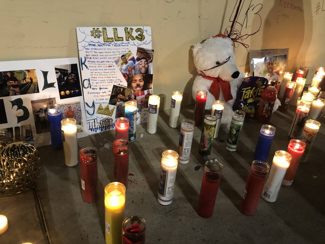 Poster boards decorated with photos of 18-year-old Kwavon'tia Thomas is surrounded by candles during a vigil on Friday, December 28, 2018, where he was shot Christmas Eve in a parking lot near Eas ...
