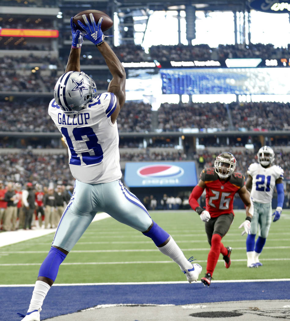 Dallas Cowboys wide receiver Michael Gallup (13) catches a touchdown pass as Tampa Bay Buccaneers safety Andrew Adams (26) looks on in the second half of an NFL football game in Arlington, Texas, ...