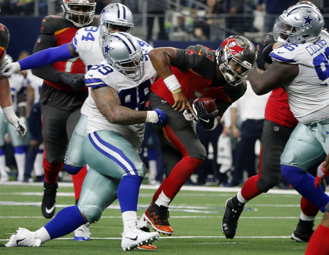 Dallas Cowboys defensive tackle Antwaun Woods (99) wraps up Tampa Bay Buccaneers quarterback Jameis Winston (3) in the second half of an NFL football game in Arlington, Texas, Sunday, Dec. 23, 201 ...