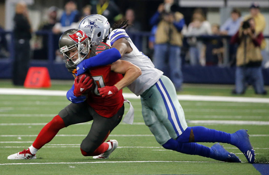 Tampa Bay Buccaneers wide receiver Adam Humphries (10) is stopped from gaining extra yardage after catching a pass by Dallas Cowboys linebacker Jaylon Smith, right, in the second half of an NFL fo ...
