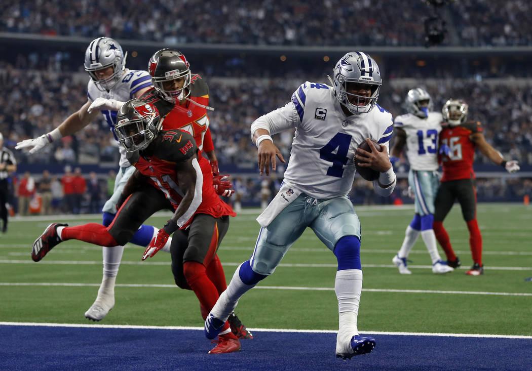 El quarterback de los Cowboys de Dallas, Dak Prescott (4), supera a los defensivos de los Buccaneers de Tampa Bay, Jordan Whitehead y Carlton Davis, para anotar un touchdown en la primera mitad de ...