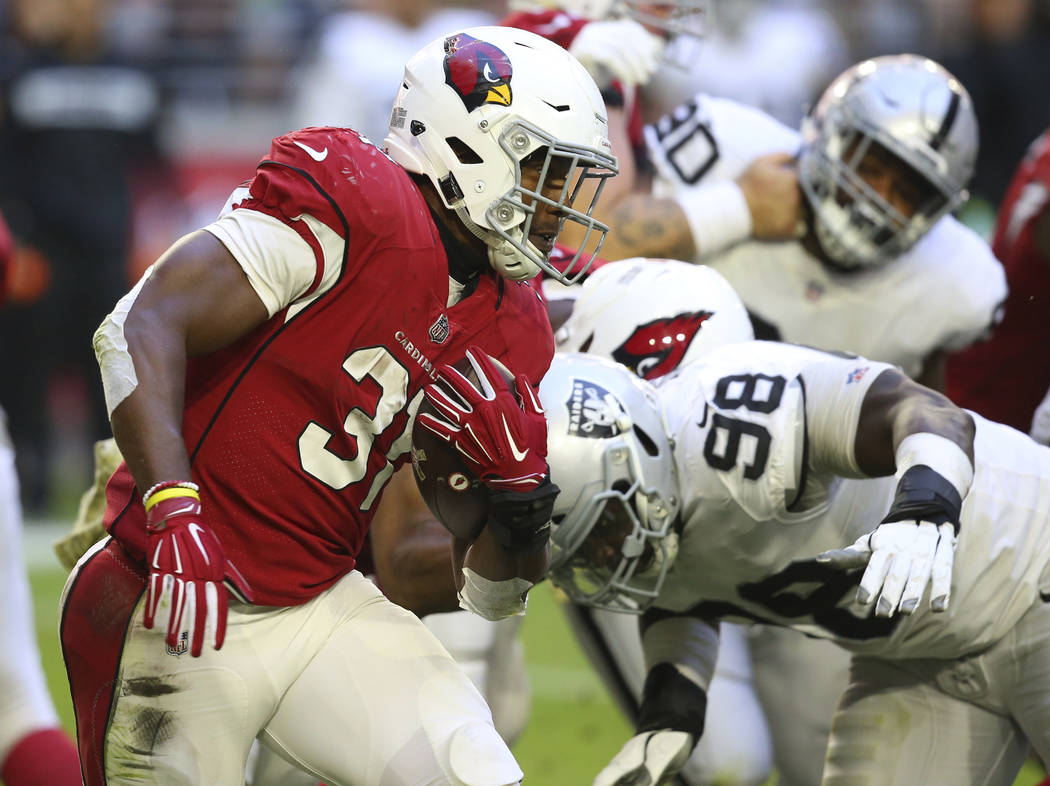 Arizona Cardinals running back David Johnson (31) runs as Oakland Raiders defensive end Frostee Rucker (98) makes the hit during the first half of an NFL football game, Sunday, Nov. 18, 2018, in G ...