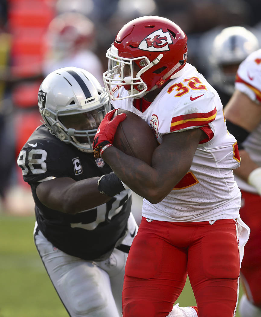 Kansas City Chiefs running back Spencer Ware (32) runs against Oakland Raiders defensive tackle Frostee Rucker (98) during an NFL football game in Oakland, Calif., Sunday, Dec. 2, 2018. (AP Photo/ ...