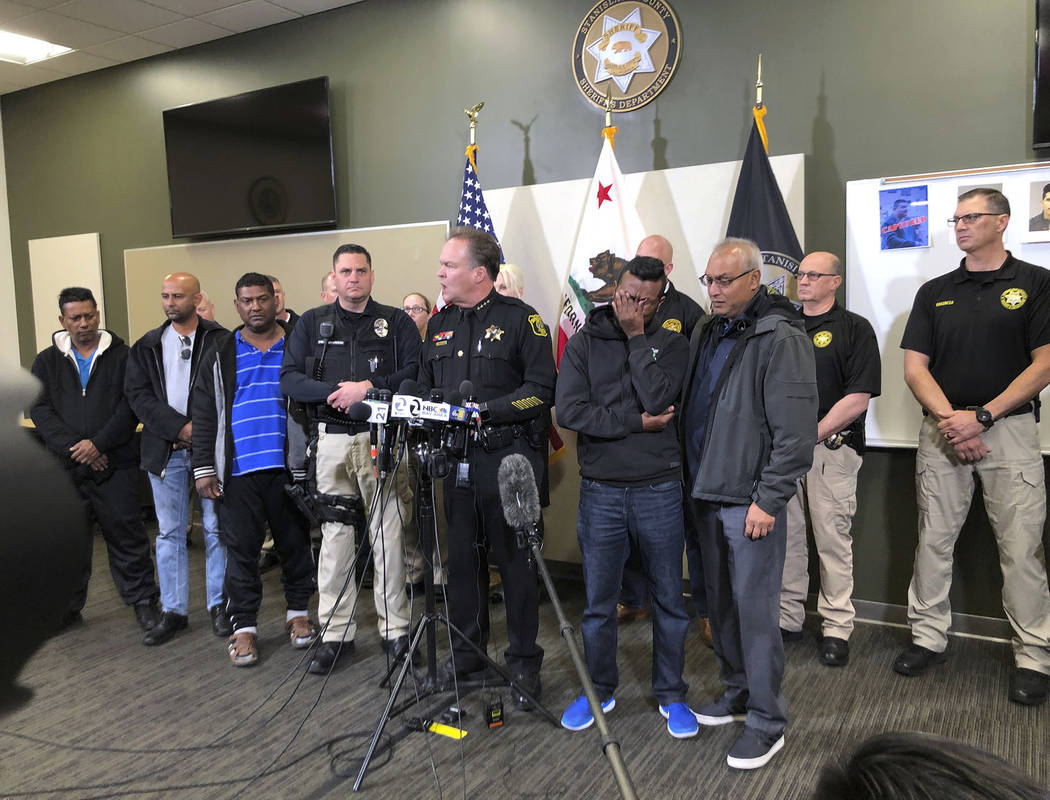 Law enforcement and family members of slain Newman Police officer Ronil Singh listen to Stanislaus County Sheriff Adam Christianson, center, talk about the arrest of suspect Gustavo Perez Arriaga ...