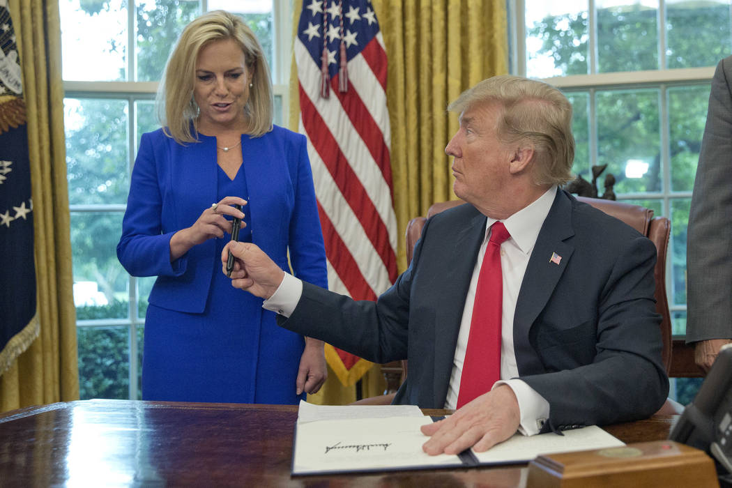 President Donald Trump gives the pen he used to sign the executive order to end family separations to Homeland Security Secretary Kirstjen Nielsen, left, during an event in the Oval Office of the ...