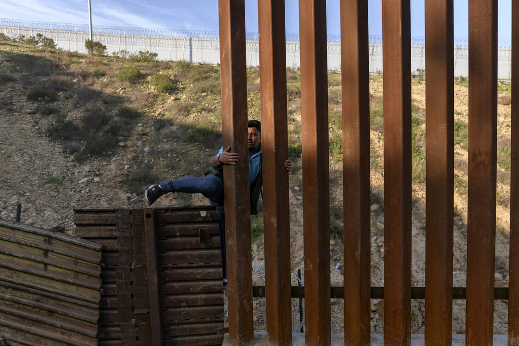 An Honduran migrant climbs the U.S. border fence to jump inside the United States to San Diego, from Tijuana, Mexico, Monday, Dec. 24, 2018. Discouraged by the long wait to apply for asylum throug ...