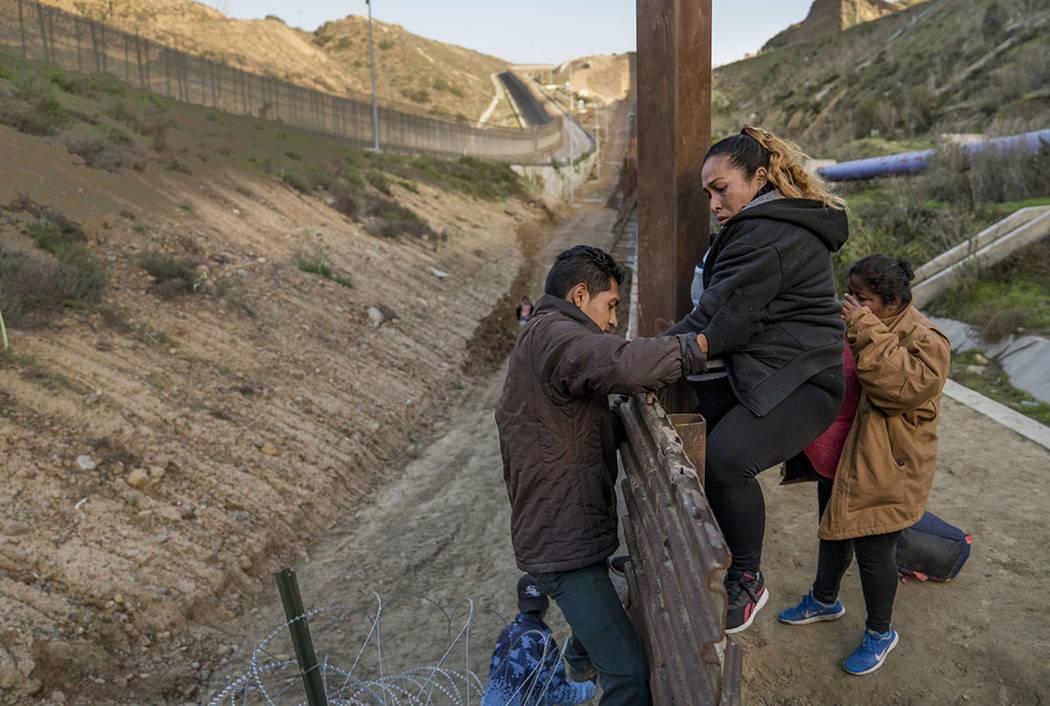A pregnant migrant climbs the border fence before jumping into the U.S. to San Diego, Calif., from Tijuana, Mexico, Thursday, Dec. 27, 2018. (AP Photo/Daniel Ochoa de Olza)