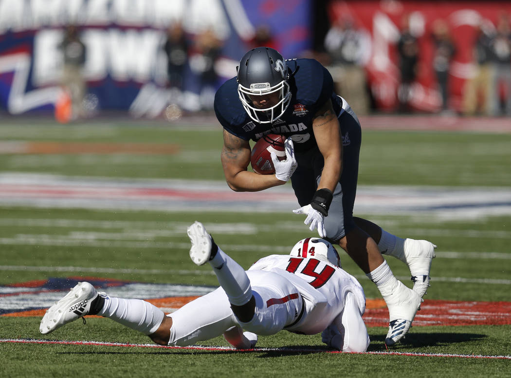 UNR tight end Trae Carter-Wells breaks the tackle on Arkansas State defensive back Antonio Fletcher (14) in the first half of the Arizona Bowl NCAA college football game Saturday, Dec. 29, 2018, i ...