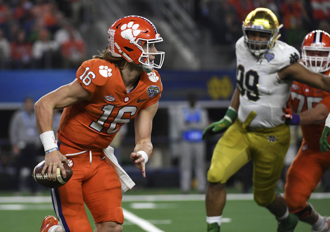 Clemson quarterback Trevor Lawrence (16) is pressured out of the pocket in the second half of the NCAA Cotton Bowl semi-final playoff football game against Notre Dame on Saturday, Dec. 29, 2018, i ...