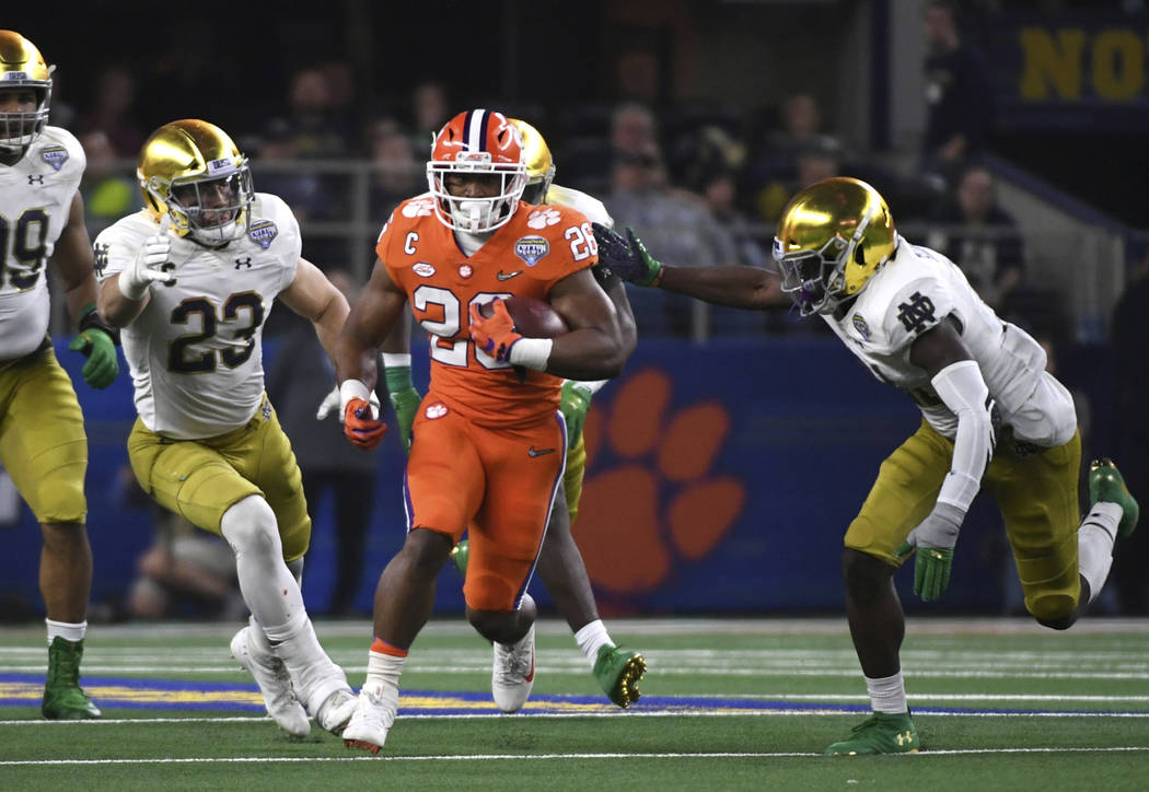 Clemson running back Adam Choice (26) runs the ball as Notre Dame linebacker Drue Tranquill (23) and others give chase in the second half of the NCAA Cotton Bowl semi-final playoff football game, ...