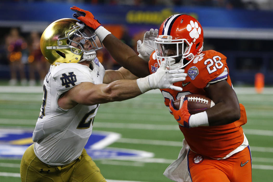 Notre Dame linebacker Drue Tranquill (23) attempts to stop Clemson running back Tavien Feaster (28) from gaining extra yardage on a running play in the second half of the NCAA Cotton Bowl semi-fin ...