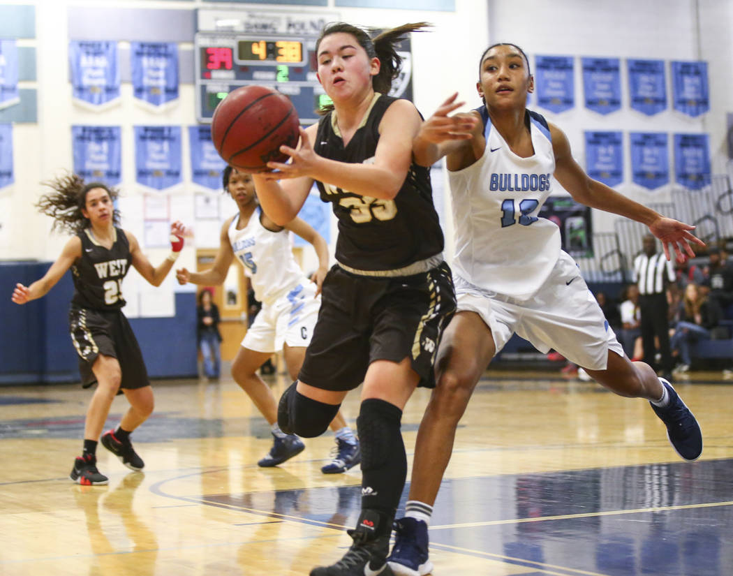 Centennial's Aishah Brown (12) tries to block a pass to West's Piper Takenaka (33) during a basketball game at Centennial High School in Las Vegas on Saturday, Dec. 29, 2018. Chase S ...